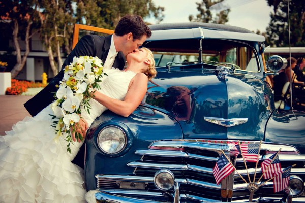 San Diego Wedding Photography: True Photography captures bride and groom kissing on classic old car retned for wedding