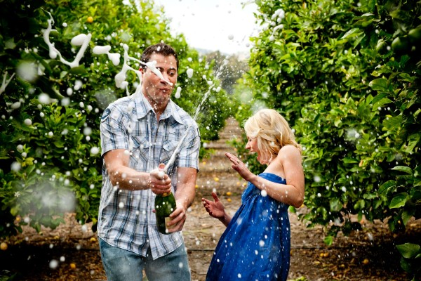 San Diego wedding photography: True Photography captures popping champagne during engagement shoot in the orange fields