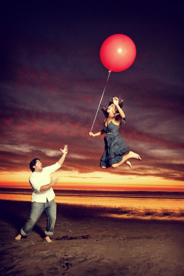 San Diego Wedding Photographer: True Photography captures girl floating away with red balloon on the beach during an engagement photo shoot in San Diego