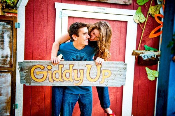 San Diego Wedding Photographer: True Photography captures couple in front of red barn with a sign as a prop
