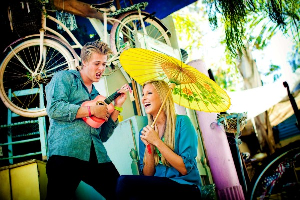 San Diego Wedding Photographer: True Photography captures Meghan and Cheyne from the Amazing Race 15 holding a guitar and umbrella during engagement shoot with props