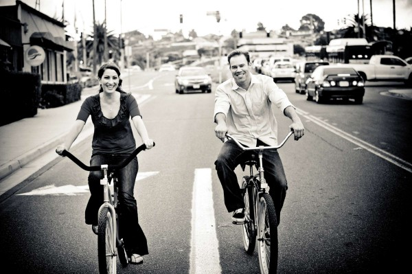 San Diego wedding photography: True Photography captures a couple riding bikes in the street during engagement shoot in San Diego