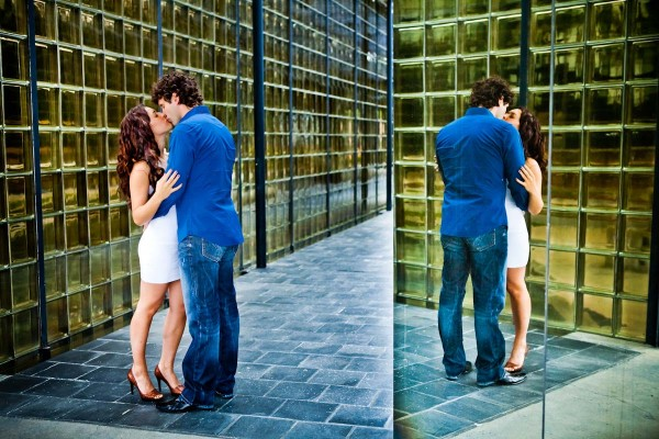 San Diego Wedding Photography: True Photography captures couple kissing during engagement shoot in front of modern mirror buildings
