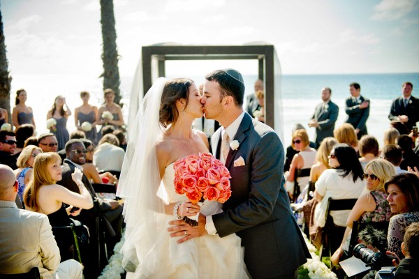 San Diego Wedding Photography: True Photography captures kiss during beach wedding ceremony at Scripps Seaside Forum