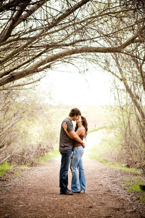 San Diego Wedding Photography: True Photography captures brunette couple in nature under the trees during engagement shoot in San Diego