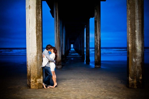 San Diego Wedding Photography: True Photography captures romantic engagement shoot of couple kissing under the pier on the beach in San Diego