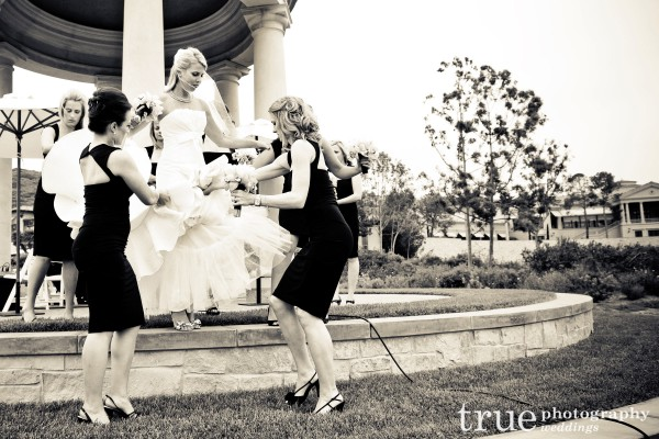 Bridesmaids in black dresses helping the bride before the ceremony at Pelican Hill Resort, Orange County