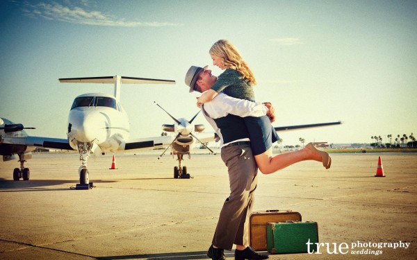 San Diego Wedding Photographer: Engaged couple seeing eachother at the San Diego airport with suitcases