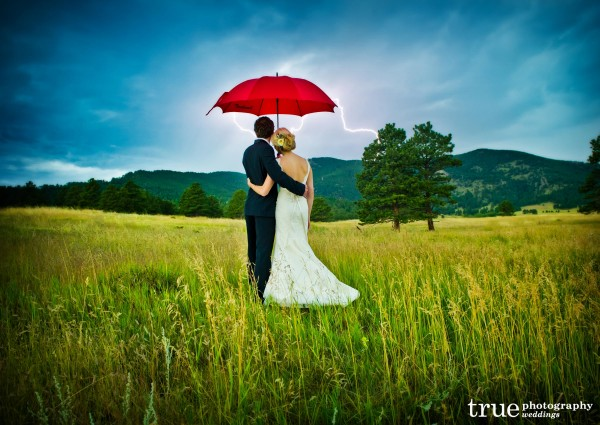 Denver wedding Photography: Bride and groom with red umbrella during lightening storm during Colorado wedding