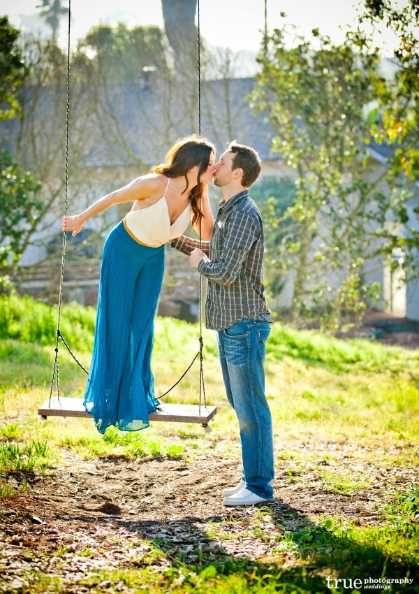 San Diego Wedding Photography: Engagement photo shoot on a swing in a filed in San Diego