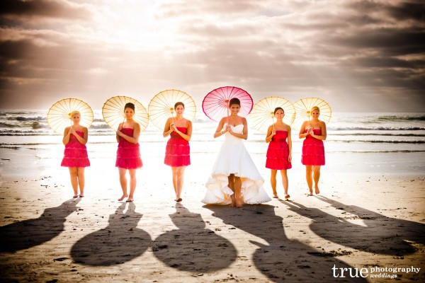 San Diego Wedding Photographer: Bride and bridesmaids walking on the beach with umbrellas at beach wedding