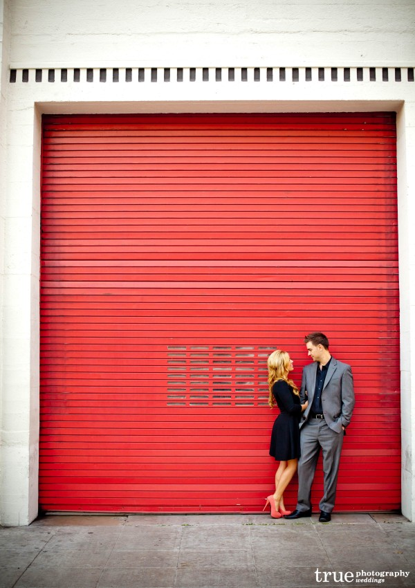 San Diego Wedding Photography: Downtown San Diego engagement photo shoot in front of bright red wall