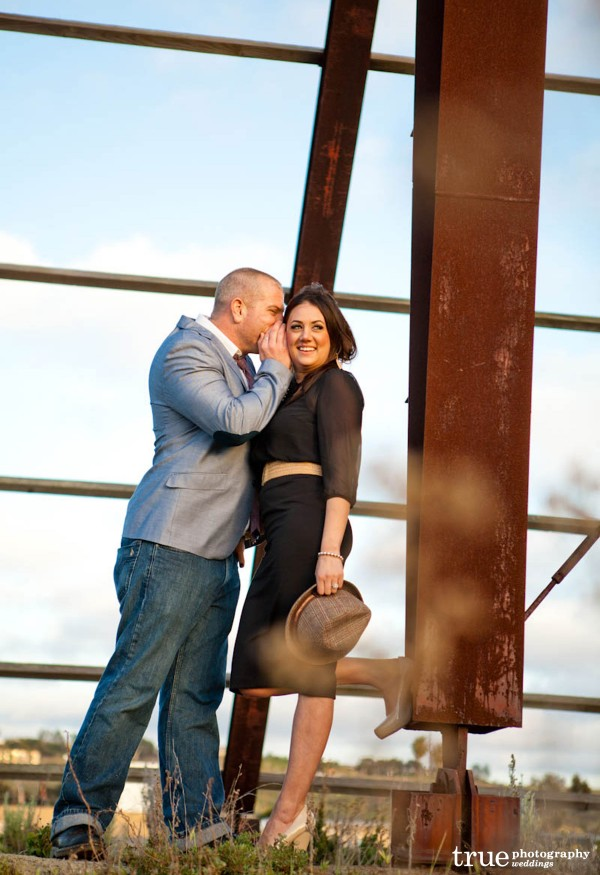 San Diego Wedding Photography: Engagement photo shoot with groom whispering secret to bride