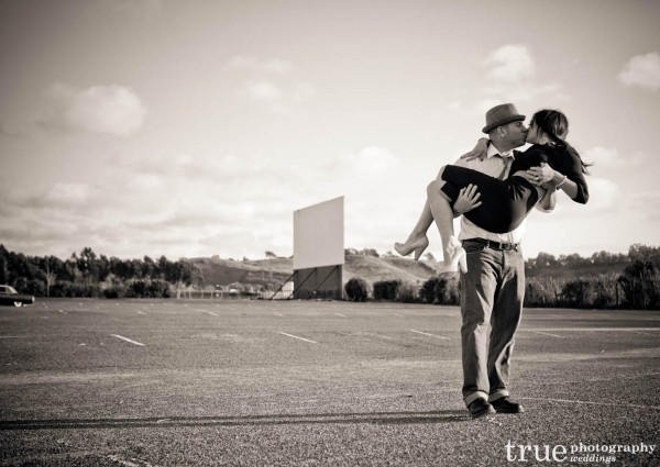 San Diego Wedding Photography: Engagement photos kissing at swap meet and drive in theatre