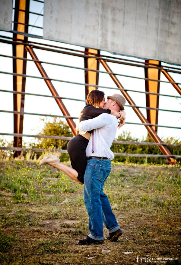San Diego Wedding Photography: Engaged couple kissing in front of Drive-In movie screen during engagement photo shoot
