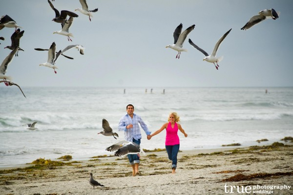 San Diego Wedding Photography: Beach engagement photos running on the beach with flying birds in Encinitas