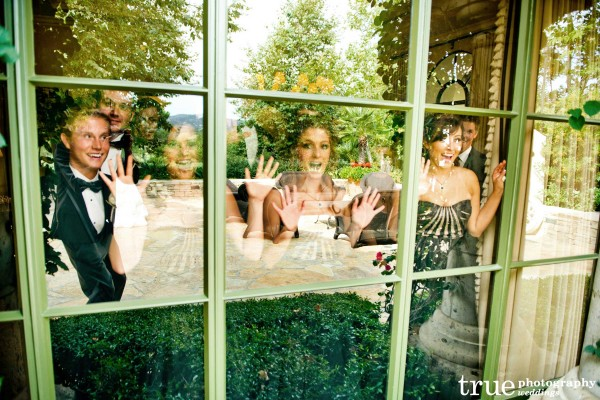 "San Diego Weddng Photographer: Wedding Party looking out window during bride and groom's ""First Look"""