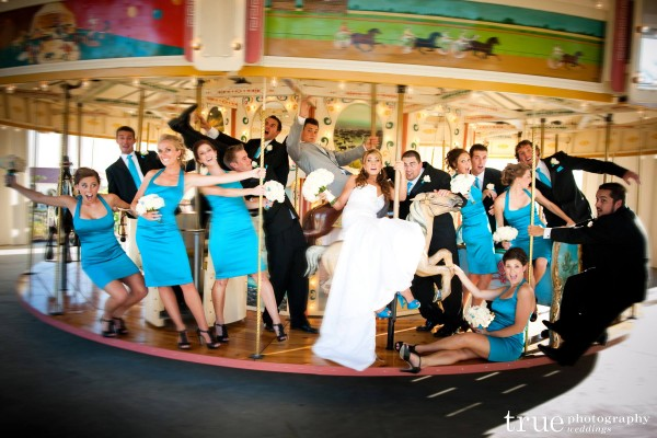 San Diego Wedding Photography: Bridal party riding the carousel at wedding in San Diego