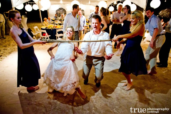 San Diego Wedding Photography: Beach wedding on the sand with bride and groom doing the limbo