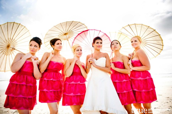 San Diego Wedding Photographer: Pink bridesmaids dresses on the beach with parasols