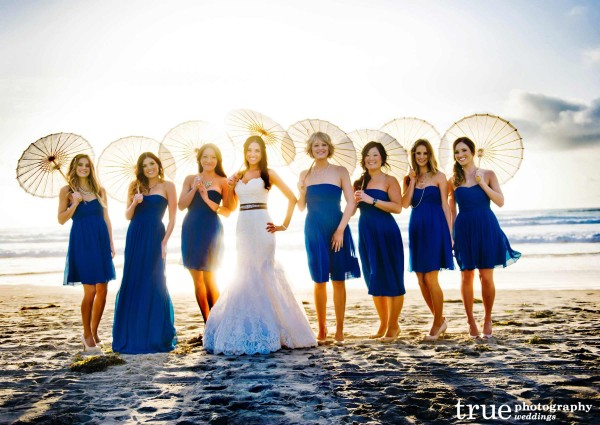 Bridesmaid on the beach with umbrellas at Scripps Seaside Forum wedding with I Do Weddings