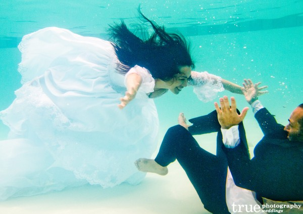Jumping into swimming pool during Underwater Engagement Shoot with True Photography