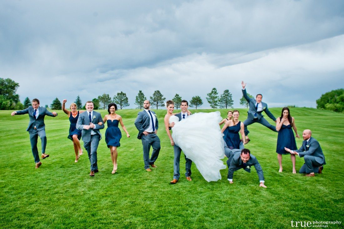 bridal party being playful in the green grass