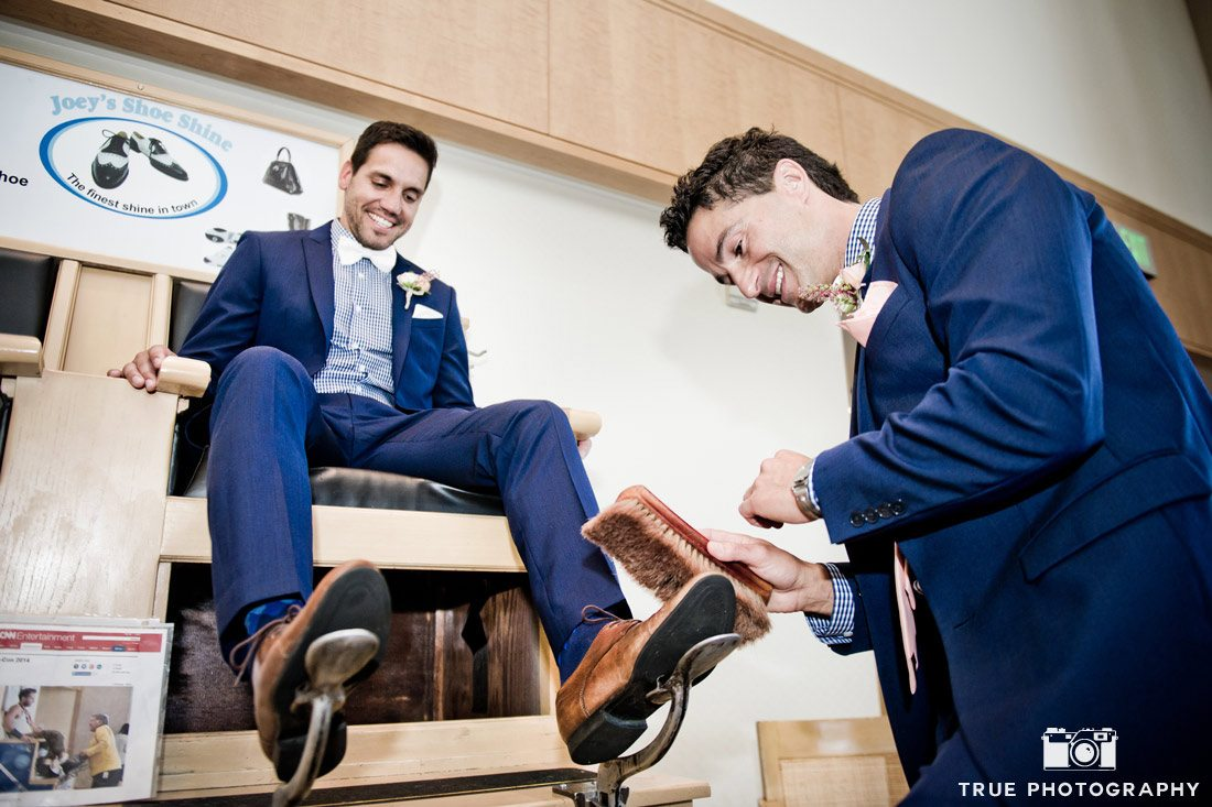 groom getting shoeshine from groomsman