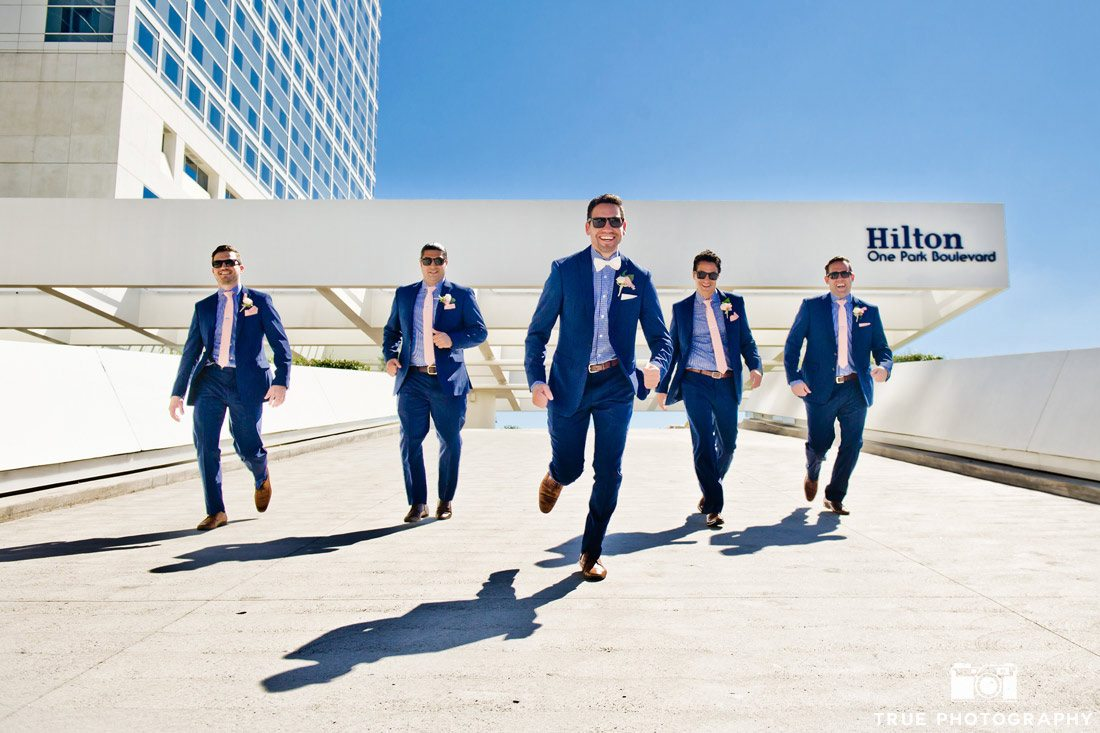 groomsmen walking in line in front of Hilton Hotel