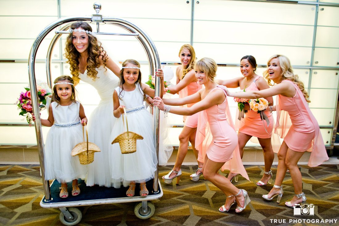 bridesmaids pushing bride and flower girls in luggage cart