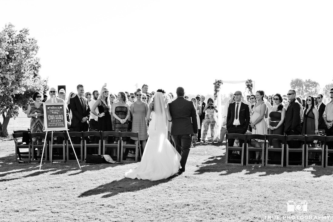 b&w bride and groom walking into ceremony