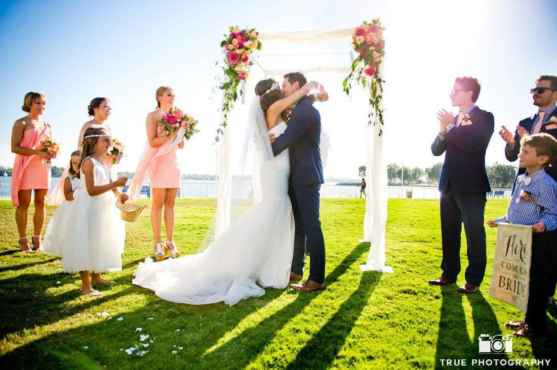 bride and groom first kiss wedding canopy near ocean