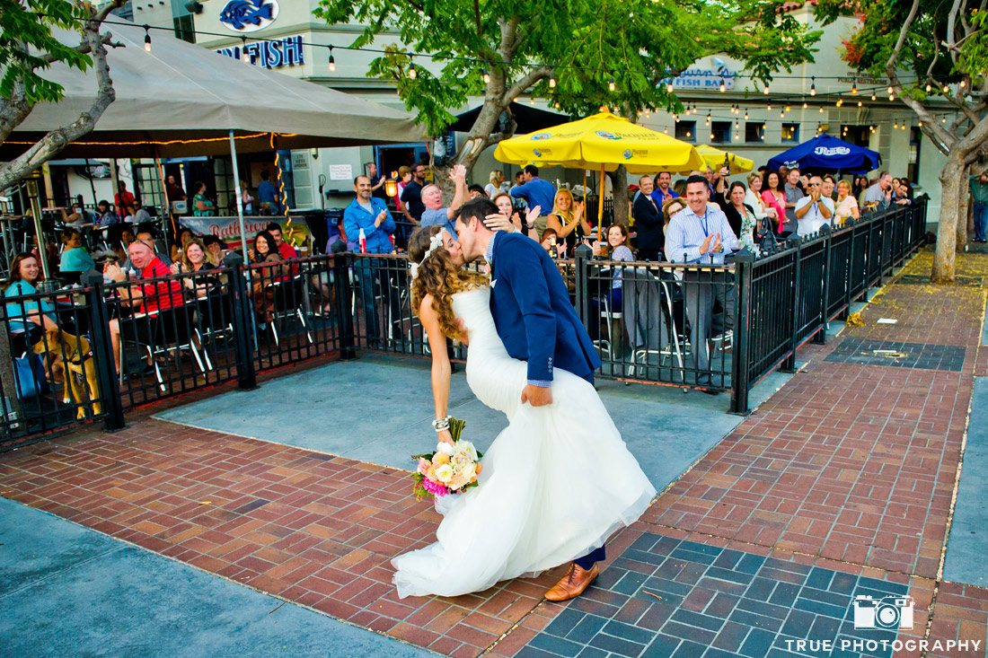 bride and groom kiss busy downtown outdoor restaurant