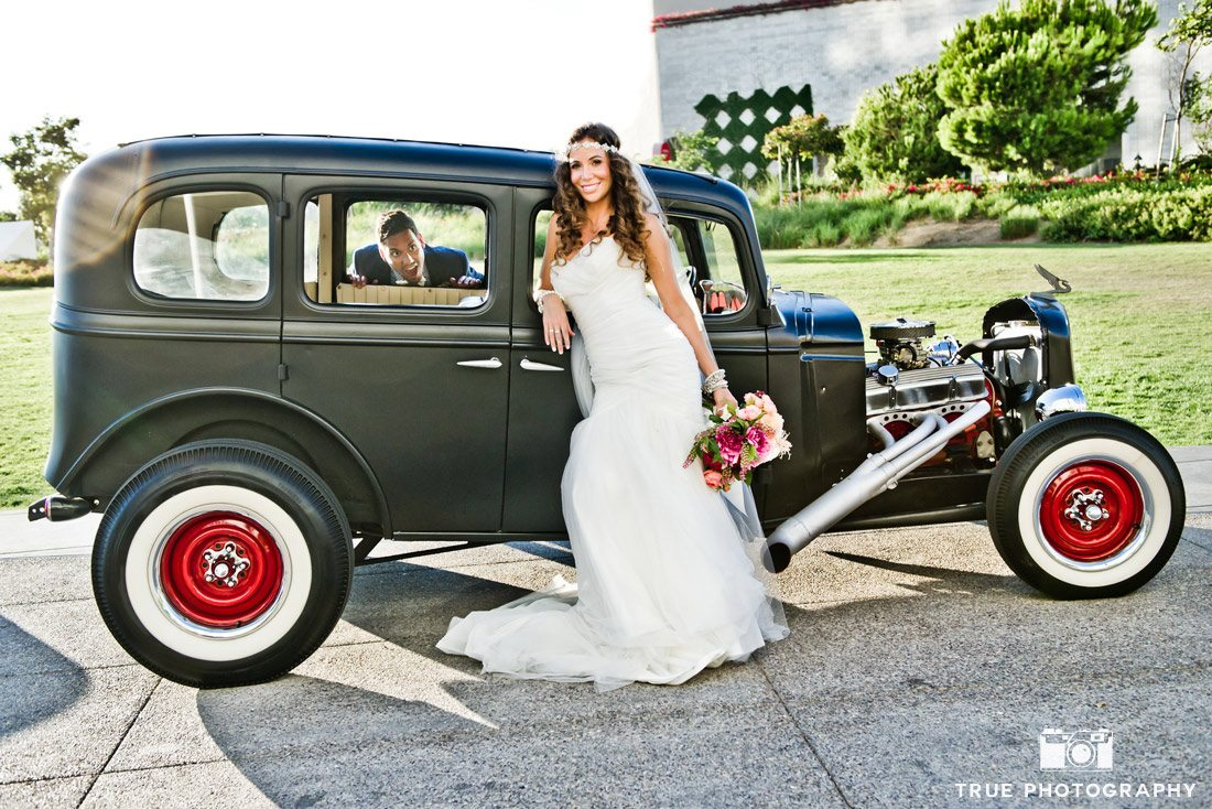 bride standing in front of classic car with groom peeking