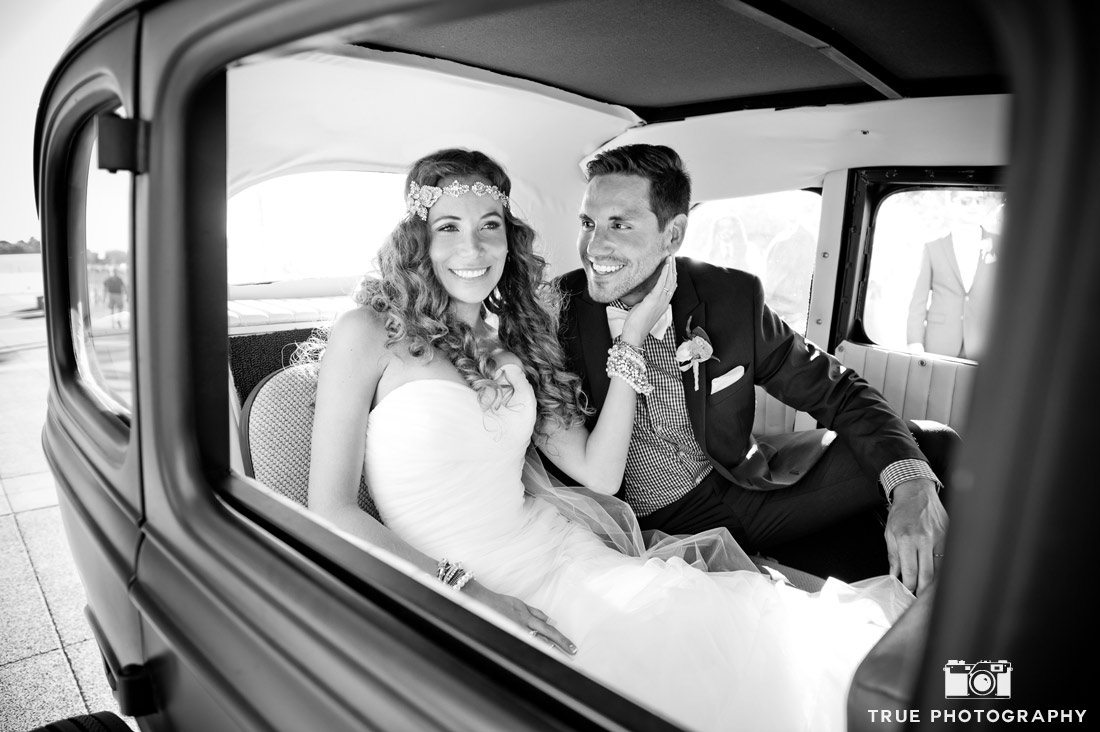 b&w bride and groom inside classic car