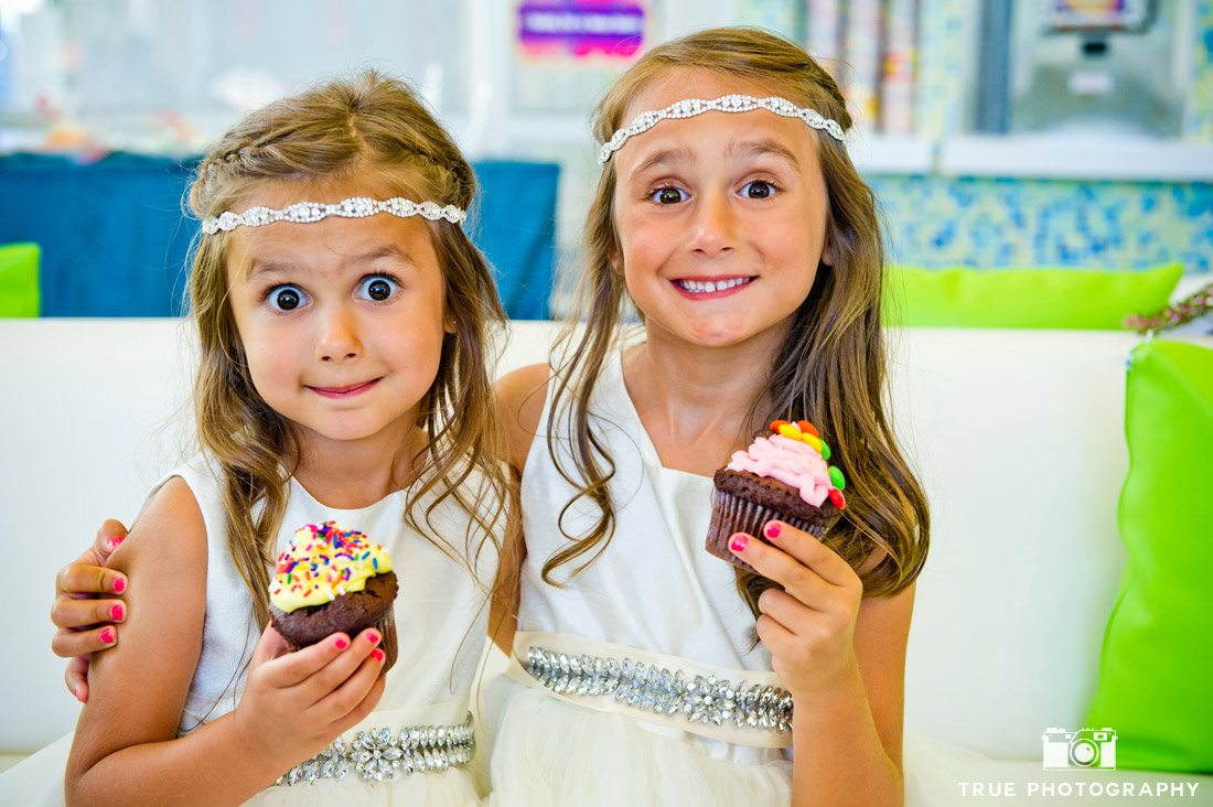 flower girls eating cupcakes in sweet shop