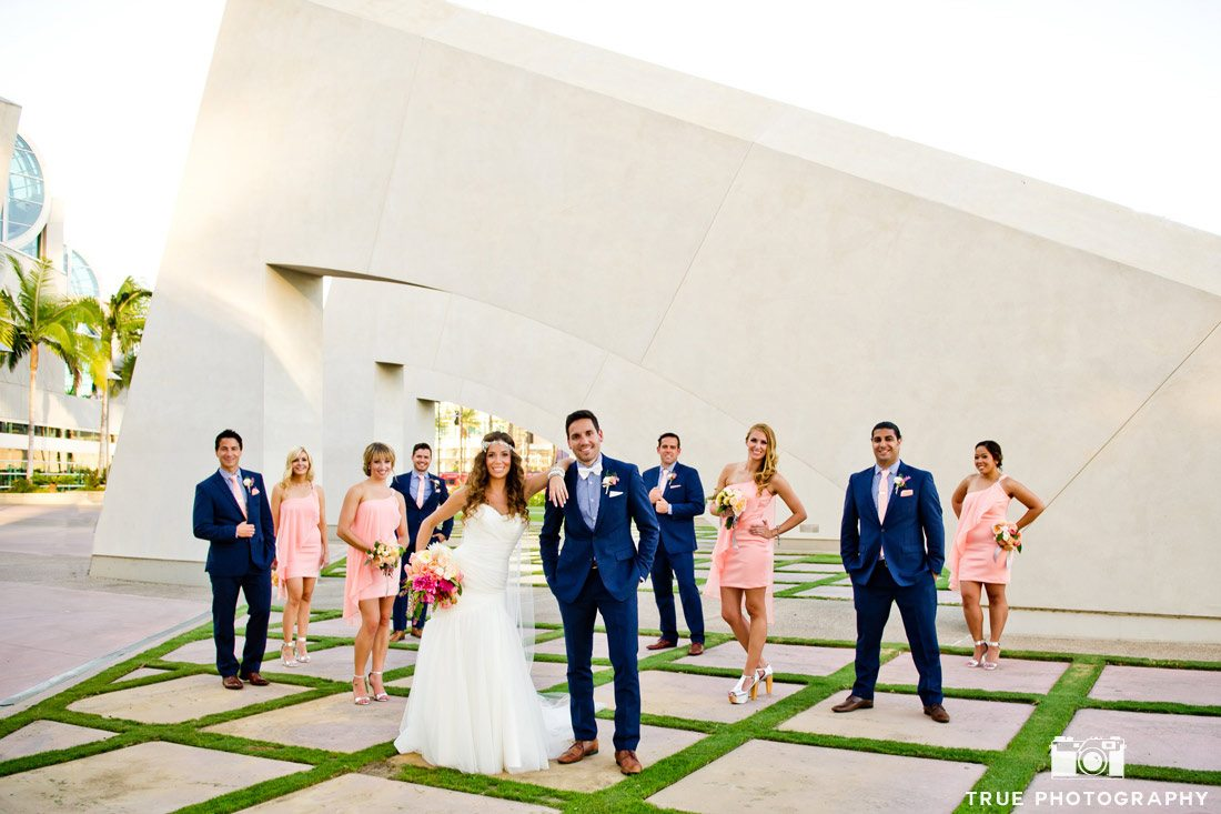 bridal party standing in front of arch on tiled lawn