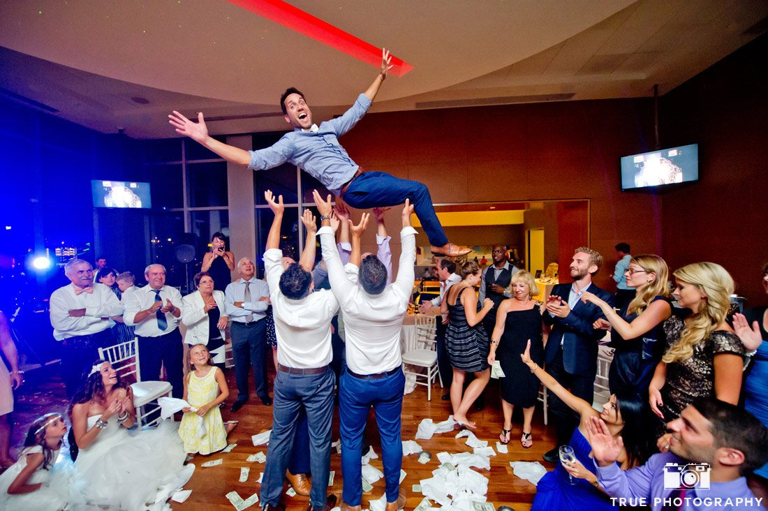 groomsmen throwing groom in the air dance floor