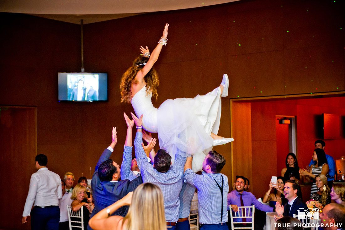 groomsmen lifting bride into the air dance floor
