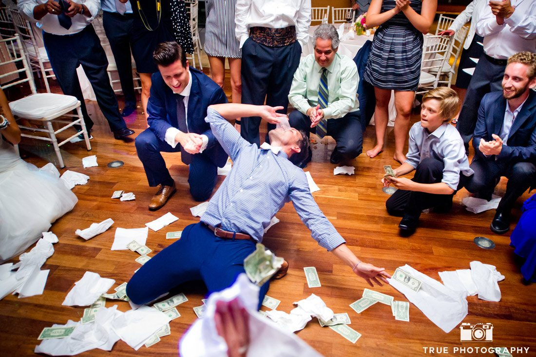 groom drinking a shot of ouzo during Greek dance