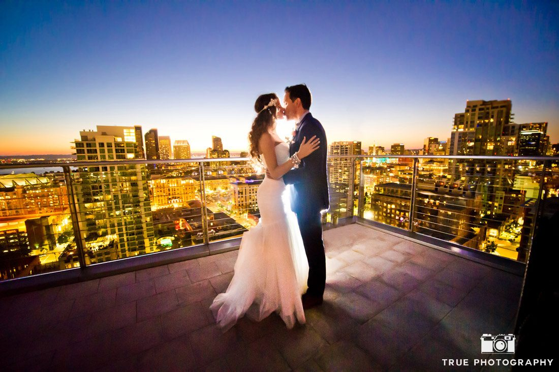 bride and groom kissing at Ultimate Skybox city view