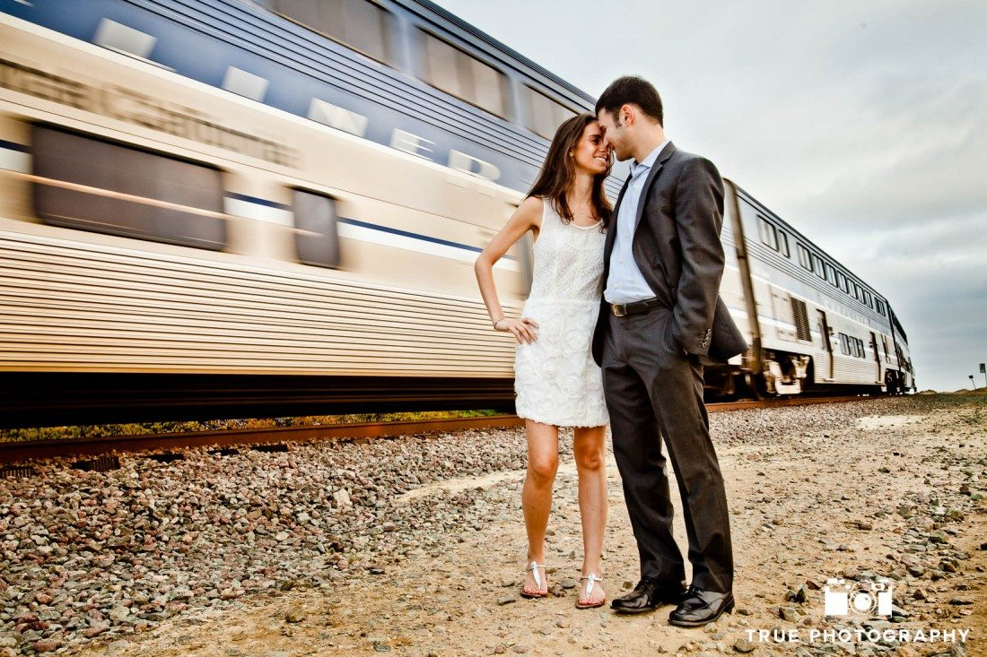 Engagement shoot of Del Mar Beach couple in front of train