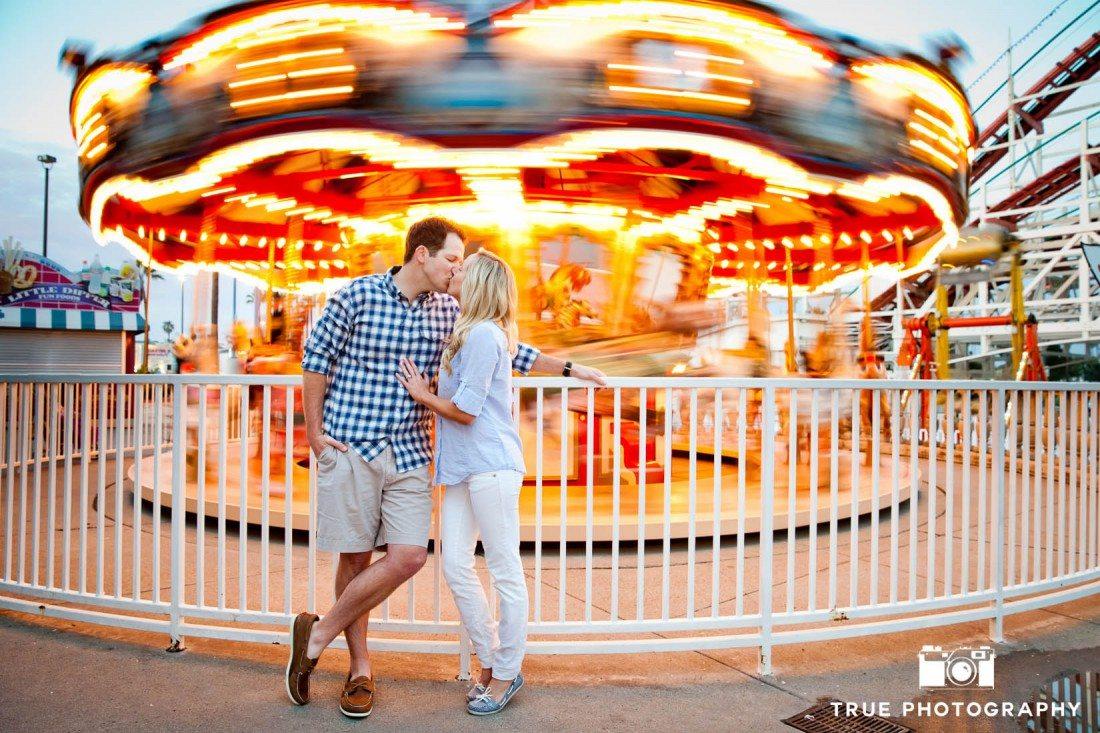 Engagement photo shoot of Mission Beach couple at carousel