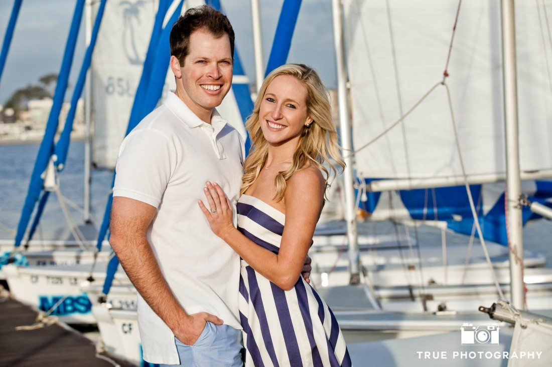 Engagement photo shoot of Mission Beach couple in front of boats