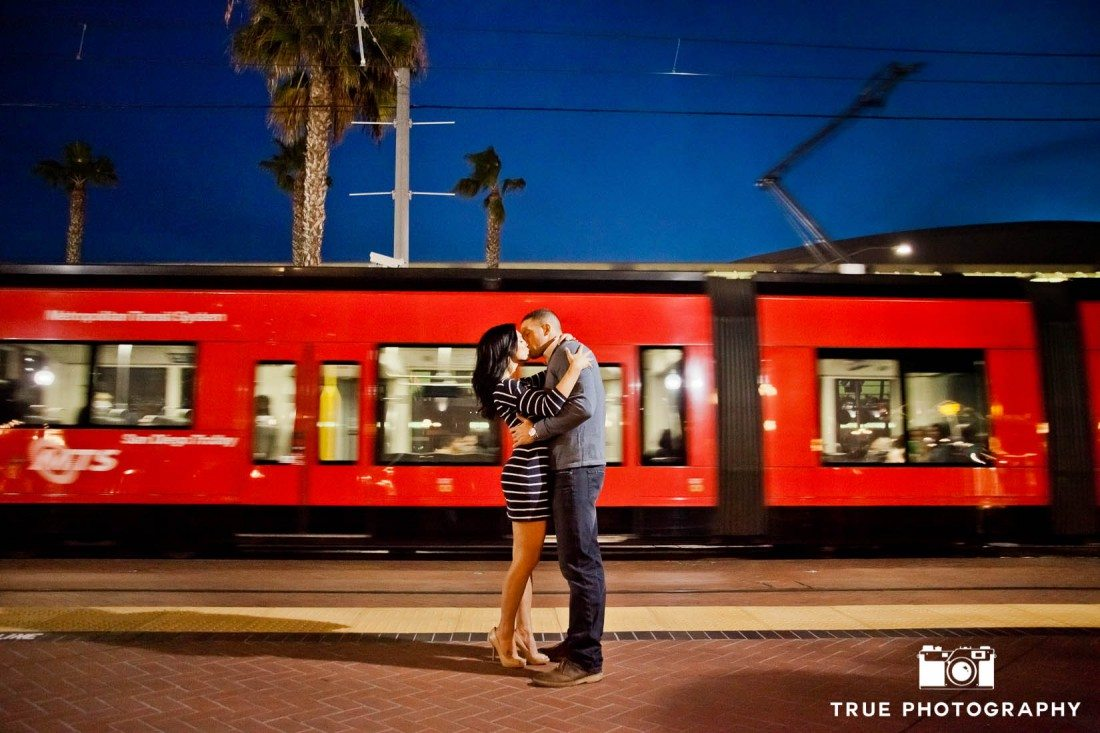 engaged couple kissing in front of trolley in Downtown San Diego
