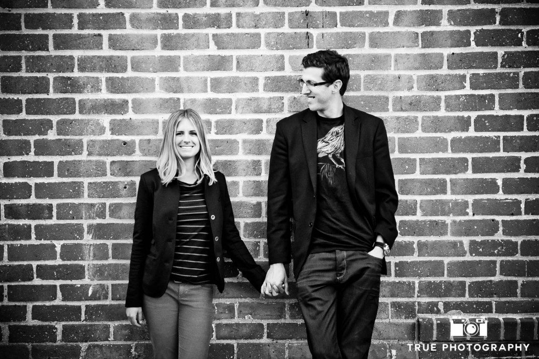 engagement photo shoot of Old Town Couple against brick wall