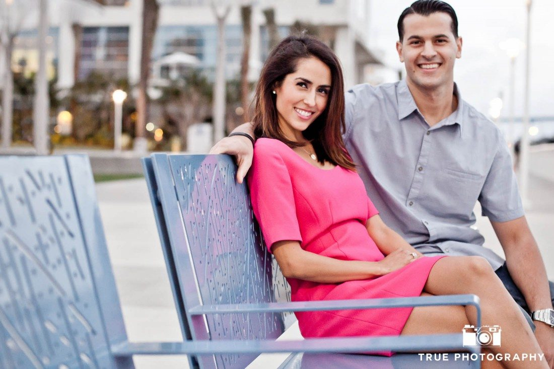 engagement shoot of couple sitting at Harbor Drive Pedestrian Bridge
