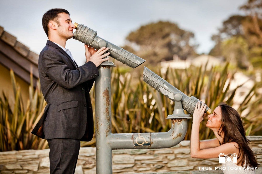 Engagement shoot of Del Mar Beach couple looking though telescope