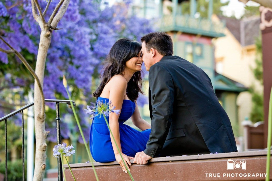 engagement photo shoot of Old Town Couple sitting with purple flowers