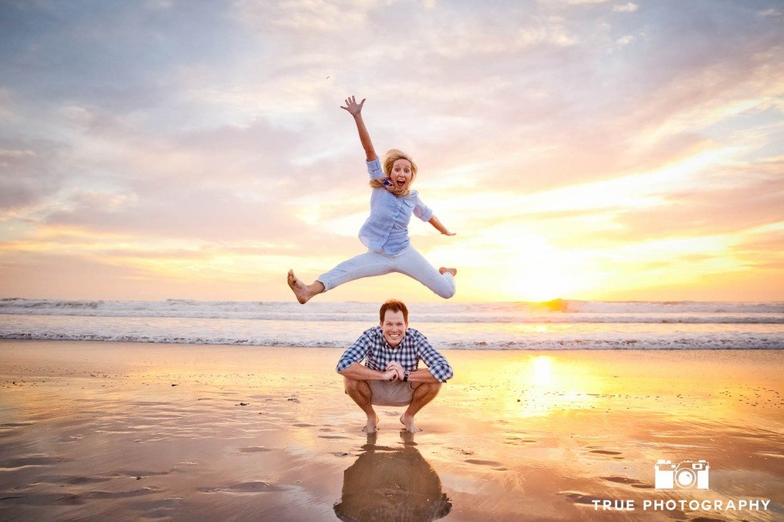 Engagement photo shoot of Mission Beach couple with the future bride jumping on beach